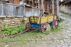 Yellow wooden cart in front of old house, Jeravna village, Bulgaria.  Royalty Free Stock Photos