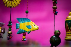 Yellow wooden fish with blue fins suspended by beaded string.  Stock Photos