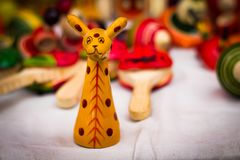 A yellow wooden giraffe figure vintage toy against a blurred background stock photo