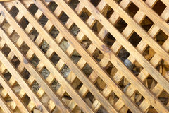 Yellow wooden grille with diamond-shaped cells. In the Stock Images