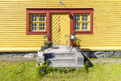 Yellow wooden house with red window frames Stock Photography