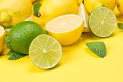 On a yellow wooden table, sliced lemons and lime together with mint leaves royalty free stock photo