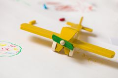Yellow wooden toy plane on the white background. Education, children, play concept. Kids drawings with the toy. Childhood. Happy. Joy. Kindergarden royalty free stock images