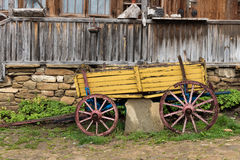 Yellow wooden waggon in front of old house in Jeravna village. Bulgaria, Europe Royalty Free Stock Photo