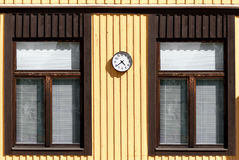 Yellow wooden wall of the two windows, and watch Stock Images