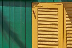 A yellow window on a green shed stock photo