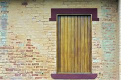 Yellow wooden window on painted apparent brick wall Stock Photos