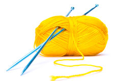 Yellow wool with needles. Yellow wool with blue needles  on white background Stock Images