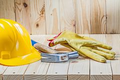 Yellow working gloves claw hammer and helmet on wooden background stock images