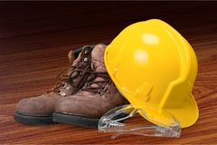 Yellow working hard hat and work boots and glasses. Boots hat work activity yellow objects background Royalty Free Stock Photos