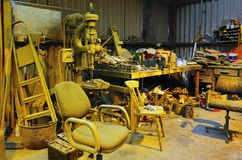 Yellow workshop chaos. The organised chaos of a working workshop. Everything is tinged with yellow, after spray painting a vehicle Stock Photo