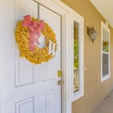 Yellow wreath with ribbon on white front door. House with a yellow ruffled wreath adorned by a red ribbon hanging on its white front door. A lamp is mounted on royalty free stock photos