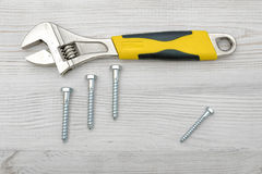 A yellow wrench and four screw bolts placed on light wooden table. Stock Photos
