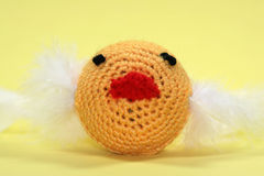 Yellow Yarn Ball Craft. A ball with a yellow yarn net around it with a red beak, black eyes, and white feathers. A great photo to highlight arts and crafts stock images
