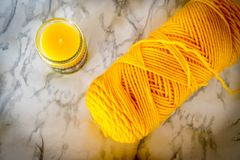 Yellow yarn skein and candle in moody flat lay format Stock Photo