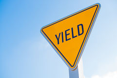 A yellow yield sign against a blue sky background Royalty Free Stock Photography
