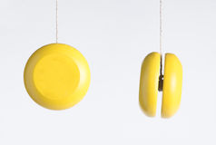Yellow yo yo. A yellow stringed toy as seen from two angles Royalty Free Stock Image