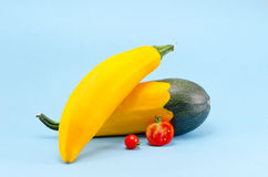 Yellow zucchini and red tomato on azure background Stock Photo