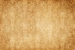 Old grunge paper with floral patterns. Yellowed grunge paper background with decorative floral patterns. Old dirty and yellowed wallpaper background for the royalty free illustration