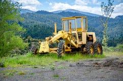 Yellowgrader on mountainous road construction. Old grader on mountainous road construction Stock Photo