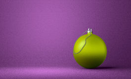 Yellowish-green Christmas ball on violet background. Yellowish-green Christmas ball on violet textured background Royalty Free Stock Image