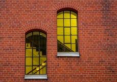 Yellowish-lit windows in a brick wall stock photo