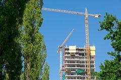 Yellows cranes working to build up concrete skeleton royalty free stock photography