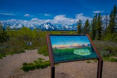 YELLOWSTONE, ΜΟΝΤΑΝΑ, ΗΠΑ ΣΤΙΣ 24 ΜΑΐΟΥ 2018: Κλείστε επάνω του πληροφοριακού σημαδιού της σειράς Teton και του τοπίου βουνών κοι Στοκ φωτογραφίες με δικαίωμα ελεύθερης χρήσης