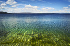 Yellowstone Lake. The green and blue waters of Yellowstone Lake are accentuated here by the pattern of the waves on the water. In the distance lie the Teton stock photo