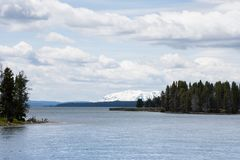 Yellowstone Lake with Mountains. Yellowstone Lake with snow capped Rocky Mountains in the distance and a forest in the midground. Dense clouds hang over the lake stock photos