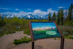 YELLOWSTONE, MONTANA, EUA 24 DE MAIO DE 2018: Feche acima do sinal informativo da escala de Teton e as montanhas do vale ajardina Fotos de Stock Royalty Free