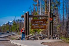 YELLOWSTONE, MONTANA, EUA 24 DE MAIO DE 2018: Mulher não identificada que espera em um sinal informativo de Teton grande em Yello Imagens de Stock