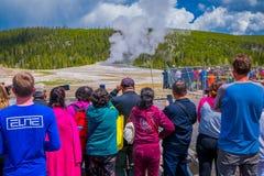 YELLOWSTONE, MONTANA, USA AM 24. MAI 2018: Touristen, die das alte zuverlässige Ausbrechen in Yellowstone Nationalpark aufpassen lizenzfreies stockbild