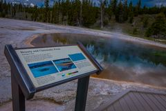 YELLOWSTONE, MONTANA, USA MAY 24, 2018: Informative sign of chromatic pools at hot spring and orange microbial mat in. The old faithful geyser basin of Stock Photos
