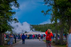YELLOWSTONE, MONTANA, USA MAY 24, 2018: Outdoor view of crowd of tourists watching and taking pictures of the Old stock photo