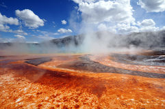 Yellowstone National Park Steam Vents. Brightly colored geothermal steam vent at Yellowstone National Park against bright blue skies with white clouds Stock Photos