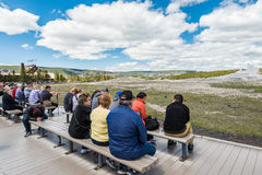 Yellowstone National Park, USA - May 17, 2016: Tired tourists sitting and waiting for the eruption of Old Faithful Geyser Stock Photos