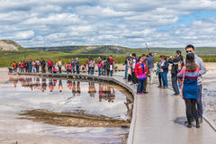 Yellowstone National Park, USA - May 17, 2016: Tourists taking pictures from boardwalk in Grand Prismatic spring in Midway Geyser Stock Images