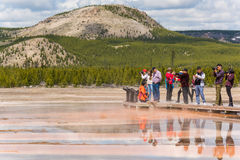 Yellowstone National Park, USA - May 17, 2016: Tourists taking pictures from boardwalk in Grand Prismatic spring in Midway Geyser Royalty Free Stock Photos