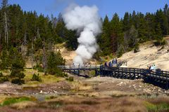 YELLOWSTONE NATIONAL PARK, WYOMING, USA - AUGUST 23, 2017:Tourists walking along the path to the Dragons Mouth Spring Stock Photography