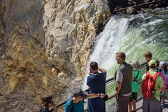 YELLOWSTONE NATIONAL PARK, WYOMING, USA - JULY 17, 2017: Organized group of tourists with a guide watching and taking pictures of. Organized group of tourists Stock Photo