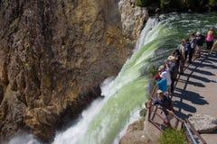 YELLOWSTONE NATIONAL PARK, WYOMING, USA - JULY 17, 2017: Tourists watching Lower Yellowstone Falls. Grand Canyon of Yellowstone Pa Stock Images