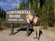 YELLOWSTONE NATIONALPARK, WYOMING, USA - AUGUSTI 23, 2017: Manligt turist- stående framme av tecknet för kontinental skiljelinje Royaltyfria Bilder