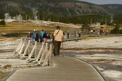 YELLOWSTONE NATIONALPARK, WYOMING, USA - AUGUSTI 23, 2017: Turister som promenerar träbanan i övregeyseren Arkivbilder