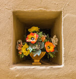 Yeloow wall niche with a pot of flowers Royalty Free Stock Images