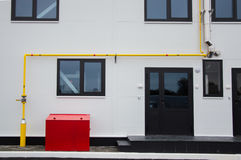 Yelow natural gas pipe, stainless steel flue pipe and red fire box installed in front of the modern building. Yelow natural gas pipe, stainless steel flue pipe stock photos