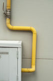 Yelow pipes and gas meter on gray wall Royalty Free Stock Images