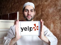 Yelp company logo. Logo of Yelp on samsung tablet holded by arab muslim man. Yelp is an American multinational corporation. It develops, hosts and markets Yelp Stock Photo