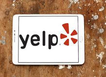 Yelp company logo. Logo of Yelp on samsung tablet on wooden background. Yelp is an American multinational corporation. It develops, hosts and markets Yelp.com Royalty Free Stock Photos