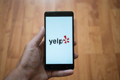 Yelp logo on smartphone screen. London, United Kingdom, june 5, 2017: Man holding smartphone with Yelp logo on the screen. Laminate wood background stock images